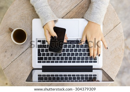 Girl with cell phone, laptop and cup of coffee - stock photo