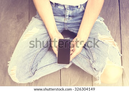 Girl with cell phone on a wooden floor