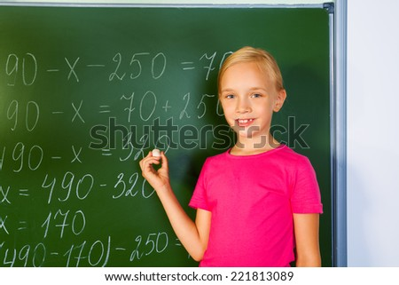 Girl with chalk in front of blackboard