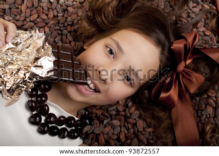 girl with chocolate on cocoa beans background