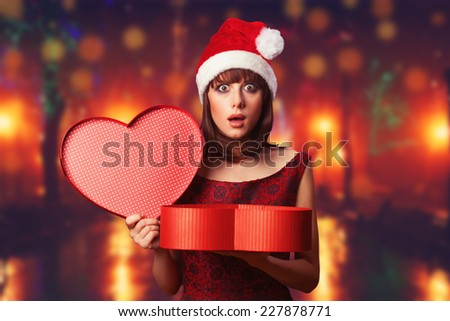 Girl with christmas box and night city on background. - stock photo