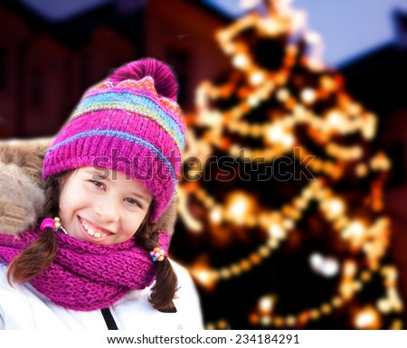 Girl with Christmas tree lights behind - stock photo
