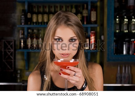 Girl with cocktail on dancing people background - stock photo