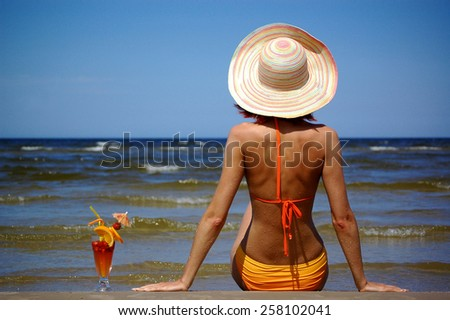 girl with cocktail on the sea - stock photo