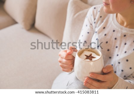 Girl with coffee mug sitting on the sofa indoors. Woman drinking a cup of  coffee or tea sitting cozy at home. Relax and rest. Cappuccino with cinnamon star. - stock photo