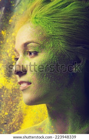 Girl with colored powder exploding around her - stock photo