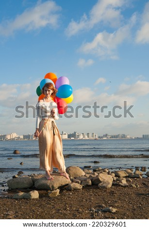 girl with colorful balloons on the rocks on the Bay