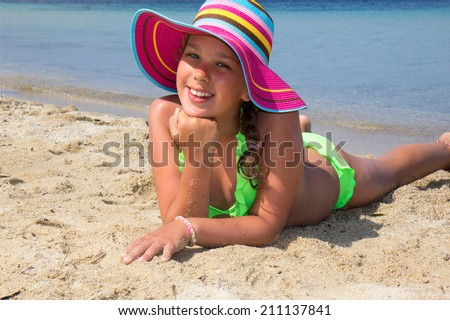 Girl with colorful hat lying on the beach