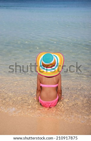 Girl with colorful hat on the beach  - stock photo