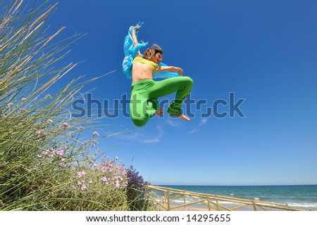 girl with colorful scarf jumping