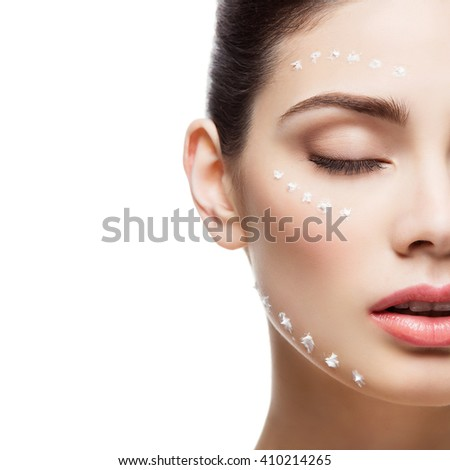 Girl with cream dots on face - stock photo