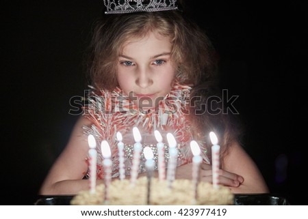 Girl with crown on head sits in dark room looking at birthday cake with burning candles.