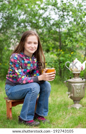 girl with cup of tea sitting at the garden  - stock photo