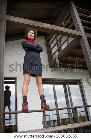 girl with curly hair in a black dress, red boots and a red scarf, the bottom view - stock photo