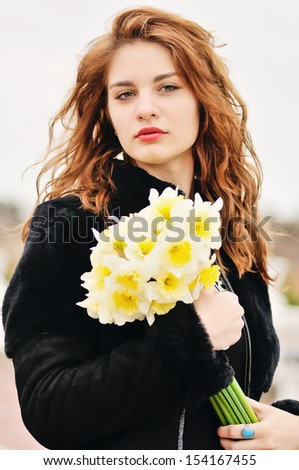 girl with daffodils in windy day - stock photo