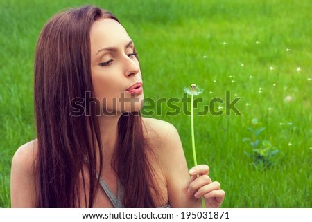 Girl with dandelion on green field - stock photo