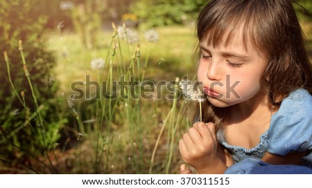 Girl with dandelions in the meadow