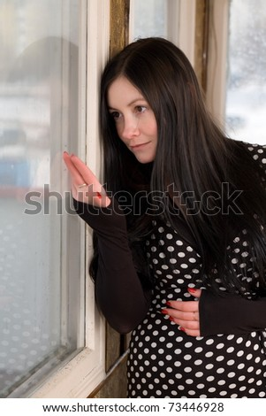 girl with dark hair looks out the window