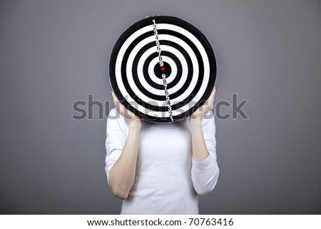 Girl with dartboard in place of head. Studio shot.