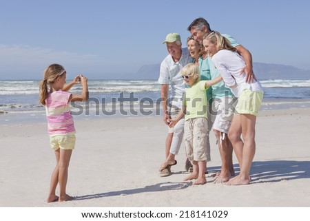 Girl with digital camera photographing multi-generation family on sunny beach - stock photo