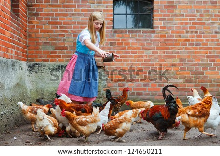 girl with dirndl feeding the chicken - stock photo