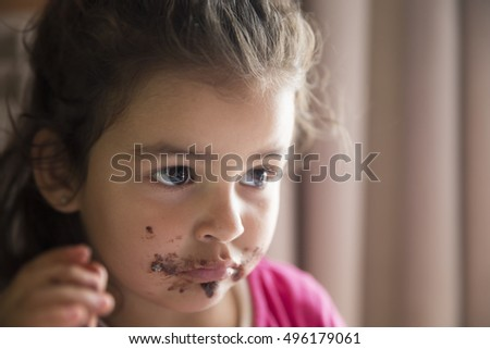 Girl with dirty mouth eating chocolate cookie