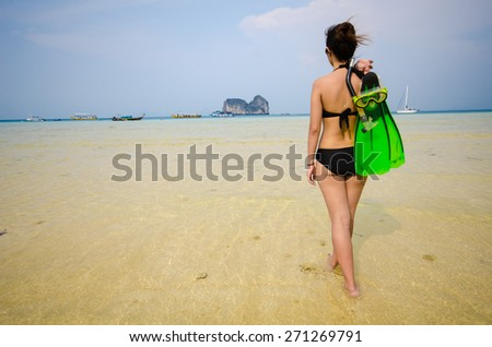 Girl with diving equipment walking on the beach - stock photo