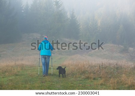 Girl with dog goes along a mountain path among x forest Trekking pole in the morning fog. Landscape composition, background mountains and sunrise. - stock photo