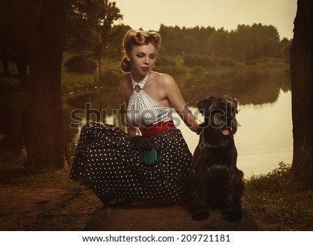 Girl with dog in a park in sunset rays. Instagram toning. Retro style.