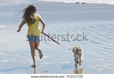 Girl with dog running on the beach - stock photo