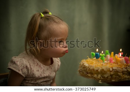 Girl with Down syndrome blows out the candles on her birthday cake - stock photo