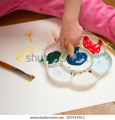 Girl with Down syndrome covered in paint when drawing - stock photo