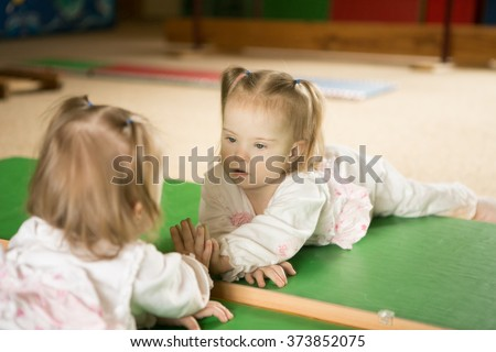 Girl with Down syndrome looks at his reflection in the mirror - stock photo