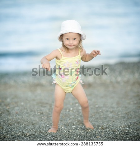 Girl with Down syndrome makes the first steps - stock photo