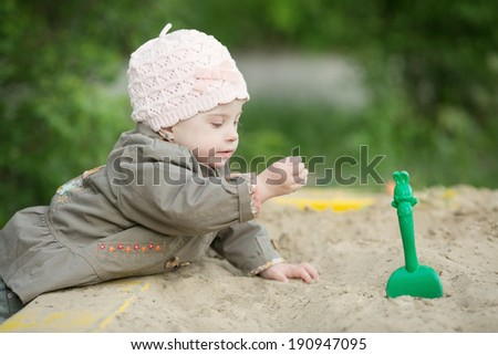 girl with Down syndrome playing in the sandbox - stock photo