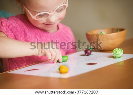Girl with Down syndrome with interest sorting vegetables - stock photo