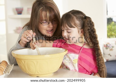 Girl with Downs Syndrome baking with mother - stock photo