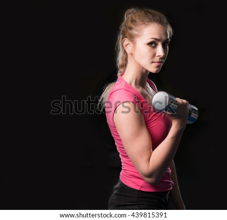 girl with dumbbells on a black background - stock photo