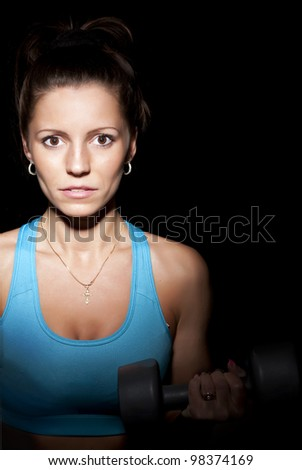 girl with dumbbells on a black background