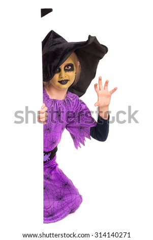 Girl with face-paint and Halloween witch costume over a white board - stock photo