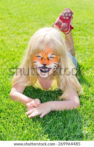 Girl with face painted as a tiger - stock photo