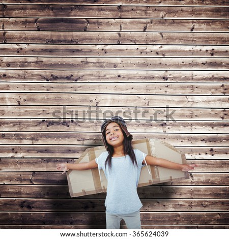 Girl with fake wings pretending to be pilot against wooden planks background - stock photo