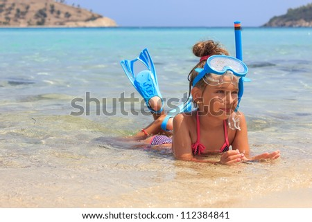 Girl with flippers lying in the sea - stock photo