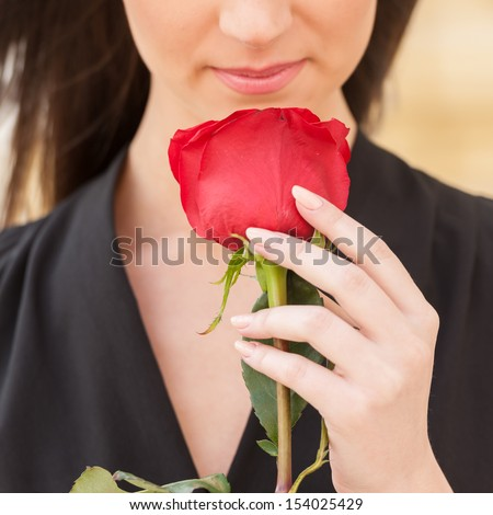 Girl with flower. Cropped image of beautiful young woman holding red rose