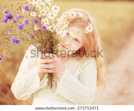 girl with flowers at field - stock photo