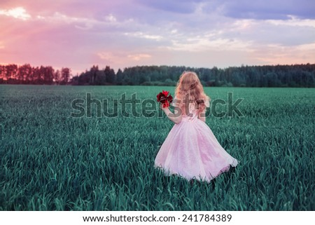 girl with flowers on field - stock photo