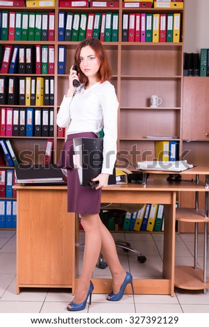 girl with folder and folder near working place - stock photo