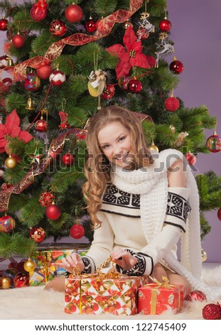 Girl with gift boxes near christmas tree - stock photo