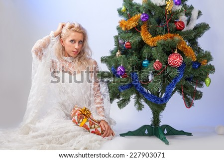 girl with gifts near a Christmas tree - stock photo
