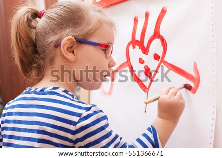 girl with glasses and a striped t-shirt paints draws paints on white  canvas